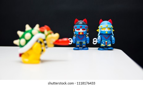 Two blue toy robots on black background and white table stand waiting for monster dog to leave.