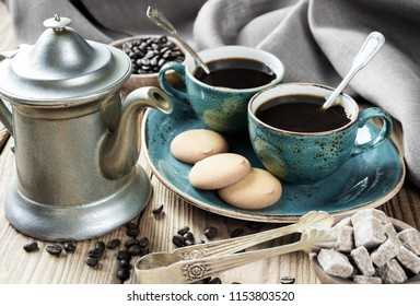 Two blue vintage cups of black coffee, biscuits and antique pewter coffee pot  surrounded by linen cloth, sugar pieces and coffee beans on old wooden table