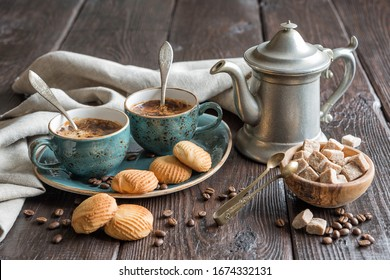 Two blue vintage cups of black coffee, cookies and antique pewter coffee pot surrounded by gray linen napkins, sugar pieces and coffee beans on old wooden table