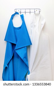Two blue and white aprons hangs on the hanger. Medical clothes for surgery on the white background.