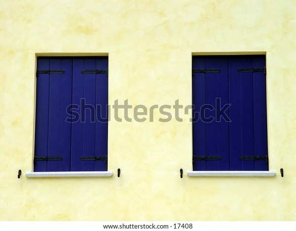 Two blue windows on a yellow wall