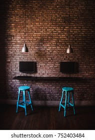 Two blue wooden stools next to desktop computers on the exposed brick interior wall of an internet cafe / co-working space