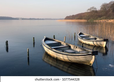 two boats floating on a quiet winter day in Denmark during sunset.