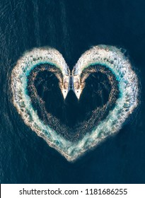 Two boats form a shape of a heart on the ocean surface; aerial top down view