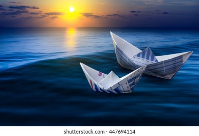 Two boats made from business paper graph on sea with sun light and sky. For business financial ideas concept.