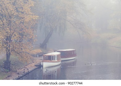 Two boats on the canal in the early foggy morning in Riga
