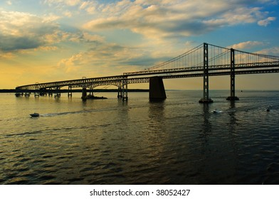 Two boats pass under Maryland's Chesapeake Bay Bridges as sunset approaches