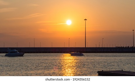 Two boats sail towards each other along the pier across the sea illuminated by the glare of the setting sun