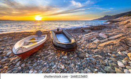 Two boats at sunset on a pebble beach on Cap Corse, Corsica, France.