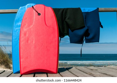 Two body boards and neoprene suits facing the beach and the ocean