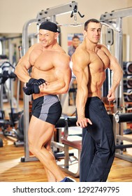 Two bodybuilders posing in a gym