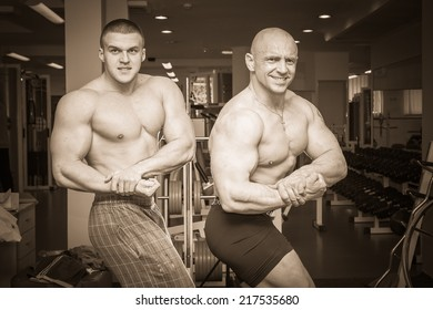Two bodybuilders posing in the gym