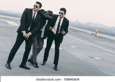 two bodyguards in sunglasses protecting businessman with gun