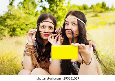 Two boho girls with long black hair making mustache taking a selfie in park on sunny summer day. Two modern young woman in hippie outfit taking self portrait. Horizontal, mild retouch, vibrant colors.