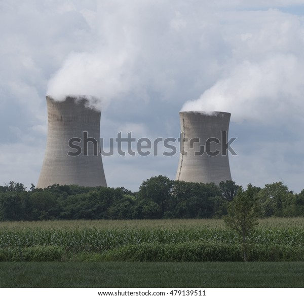 Two boiling water reactor units of the Limerick nuclear power plant northwest of Philadelphia.  The emitted water vapor merges with a cloud filled blue sky with green landscaping in the foreground.