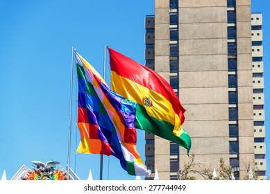 Two Bolivian flags blowing in the wind.  The checkered one is called a Wiphala