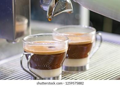 "Two ""bombon"" coffees on professional coffee machine."