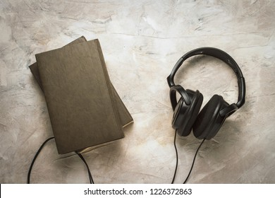 Two Books and Headphones on a white stone background. Concept Audiobooks