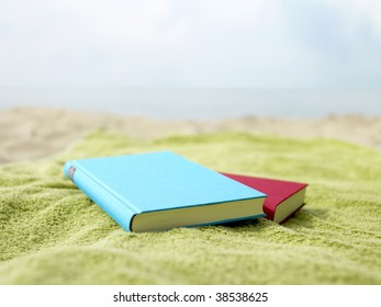 Two books lying on a towel at the beach.
