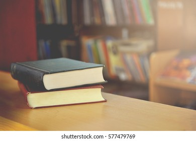 Two books stacked on wooden cabinet in the library (soft focus, Vintage).