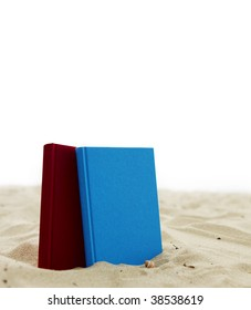 Two books standing in sand isolated on white.