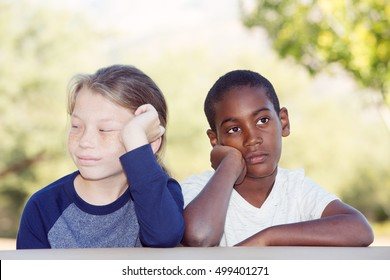Two bored adopted brothers sitting with hands on cheek waiting for something