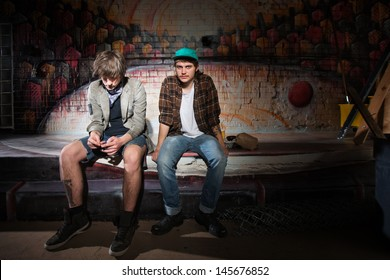 Two bored homeless white teenagers sitting outside