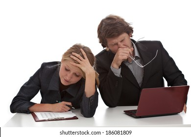 Two bored and tired business people working and yawning
