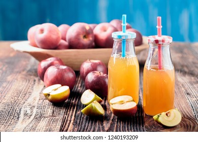 Two bottle fresh organic apple cider or apple juice on the old a wooden table.