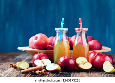 Two bottle fresh organic apple cider or apple juice with cinnamon on the old a wooden table.
