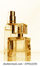 Two bottle of woman perfumes on white background. Filtered warm toned image.