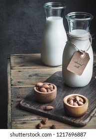 Two bottles of almond milk and wooden bowls with almonds on rustic wooden table.