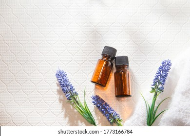 Two bottles of aromatic oil and lavender. Relaxation and beauty image.