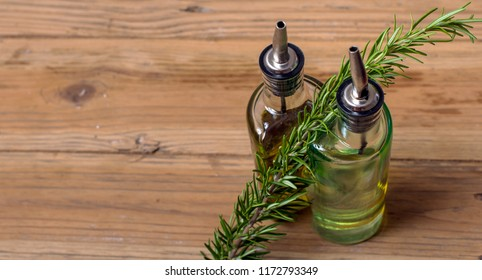 Two bottles of cooking oil with rosemary wedged between them. top view with space for text on the left. Set on wooden table.