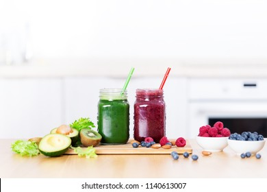 Two bottles with detox smoothie on wooden table, healthy nutririon concept, free copy space on white kitchen background, no people