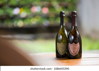 Two bottles of don perignon on a wooden surface