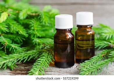 Two bottles of essential oil and fir branches. Aromatherapy and spa products