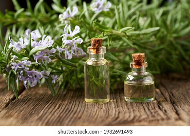 Two bottles of essential oil with fresh blooming rosemary in the background