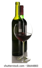 Two bottles and glass of red wine isolated on white background.