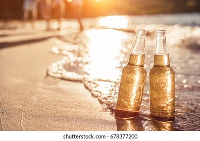 Two bottles of light beer on beach. Sea shore with waves. Group of friends on the background.