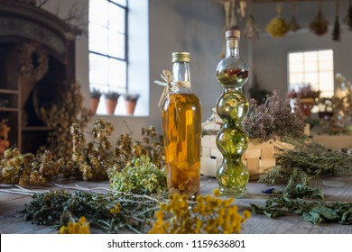 Two bottles with oil on a table with dried herbs and flowers in a workshop and studio