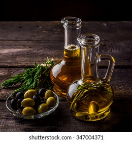 Two  bottles of olive oil, olive in a bowl and herbs on a wooden table. Selective focus.