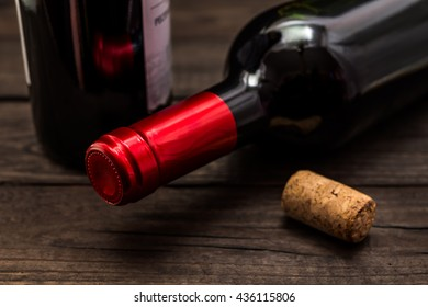 Two bottles of red wine and cork lying on an old wooden table. Close up view, focus on the bottle of red wine