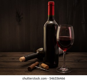 Two bottles of red wine with a glass and corkscrew with cork on an old wooden table