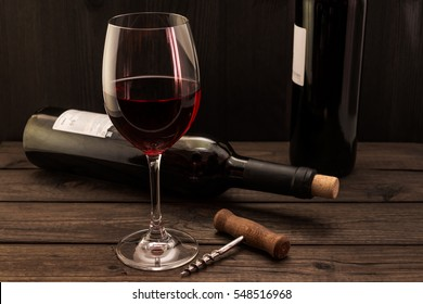 Two bottles of red wine with a glass and corkscrew on an old wooden table. Focus on the corkscrew