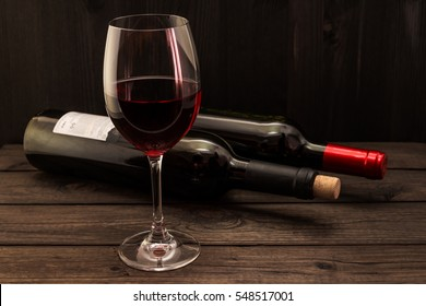 Two bottles of red wine with a glass on an old wooden table. Focus on the stem glass