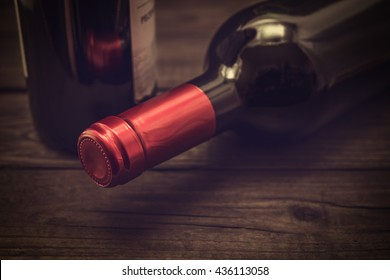 Two bottles of red wine lying on an old wooden table. Close up view, focus on the bottle of red wine, image vignetting and the yellow toning