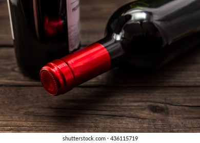 Two bottles of red wine lying on an old wooden table. Close up view, focus on the bottle of red wine
