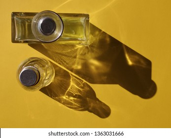 Two bottles with round caps. Abstract close-up photo of perfume, fragrance or alcohol. Flat lay of glass objects on yellow background with contrast of light and shadows.