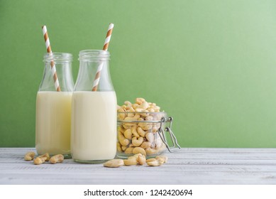 Two bottles vegetarian cashew milk with cashew nuts on green background